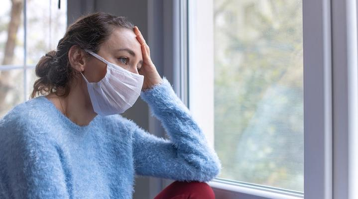 Worried woman with face mask looking out of window