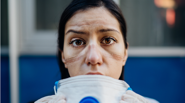 Female medical worker taking off a face mask