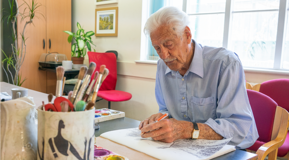 An older man focused on drawing an image of a landscape