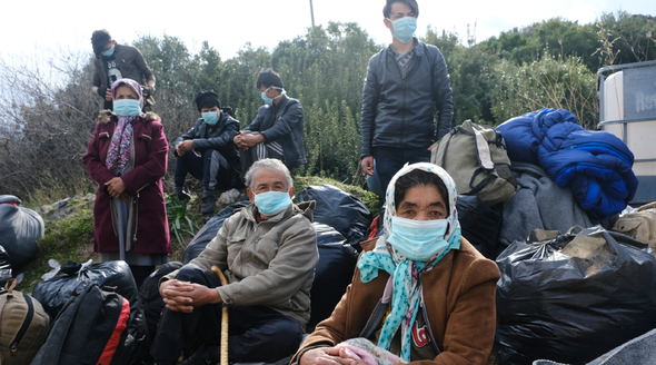 A group of migrants sitting on the ground with bags