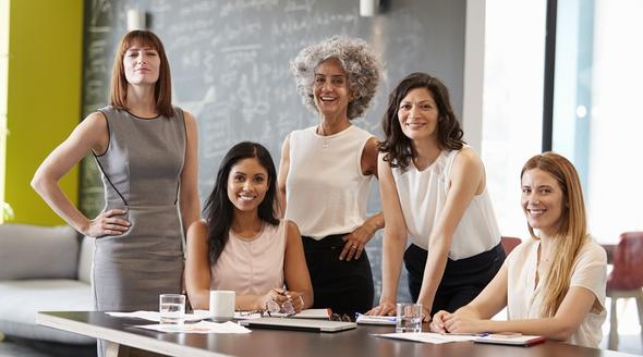Five women colleagues at a work meeting smiling to camera