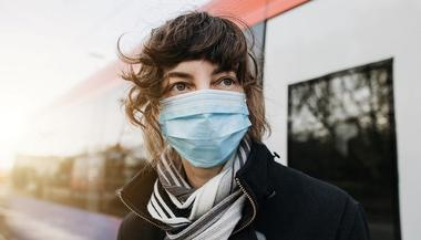 A young woman wearing a face mask stepping out of a train