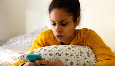 Close up portrait of a worried young woman looking at phone