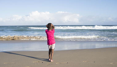 Young girl gazes out to the sea